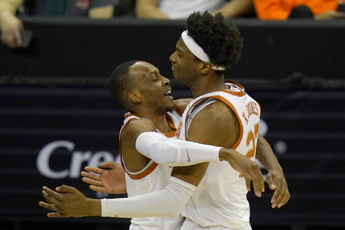 Texas guard Matt Coleman III, left, celebrates with forward Kai Jones (22) following an NCAA college basketball game against Texas Tech in the quarterfinal round of the Big 12 men's tournament in Kansas City, Mo., Thursday, March 11, 2021. Texas defeated Texas Tech 67-66. (AP Photo/Orlin Wagner)