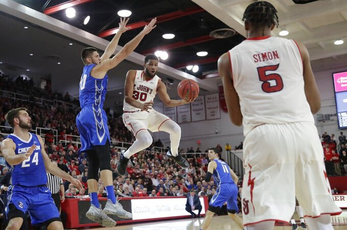 St. John's LJ Figueroa (30) passes the ball to Justin Simon (5) as he drives past Creighton's Martin Krampelj and Mitch Ballock (24) during the second half of an NCAA college basketball game Wednesday, Jan. 16, 2019, in New York. St. John's won 81-66. (AP Photo/Frank Franklin II)