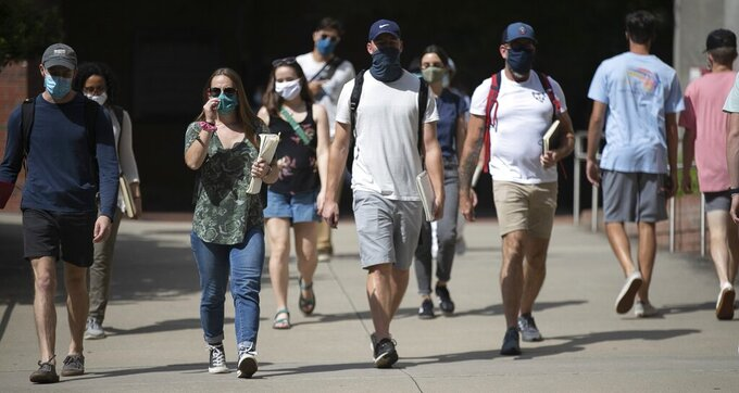 North Carolina State University students wearing face coverings walk behind Dabney Hall to the Free Expression Tunnel on Tuesday, Aug. 18, 2020 in Raleigh, N.C. The university announced Thursday, Aug. 20, 2020, it will move all undergraduate classes online starting on Monday due to COVID-19 clusters.(Robert Willett/The News & Observer via AP)