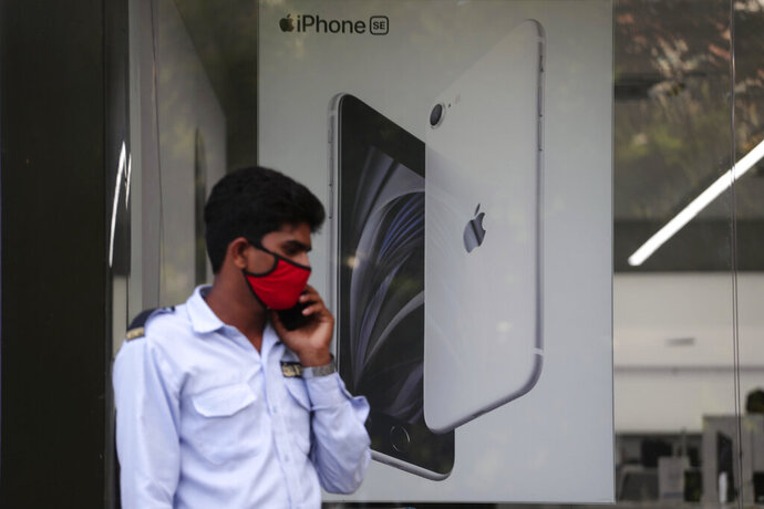 A security officer talks on a phone in front of an image of an iPhone displayed at an Apple store in Ahmedabad, India, Saturday, Aug. 1, 2020. Three contract manufacturers for Apple iPhones and South Korea's Samsung have applied for large-scale electronics manufacturing rights in India under a $6.5 billion incentive scheme announced by the government, Technology Minister Ravi Shankar Praad  said Saturday. (AP Photo/Ajit Solanki)