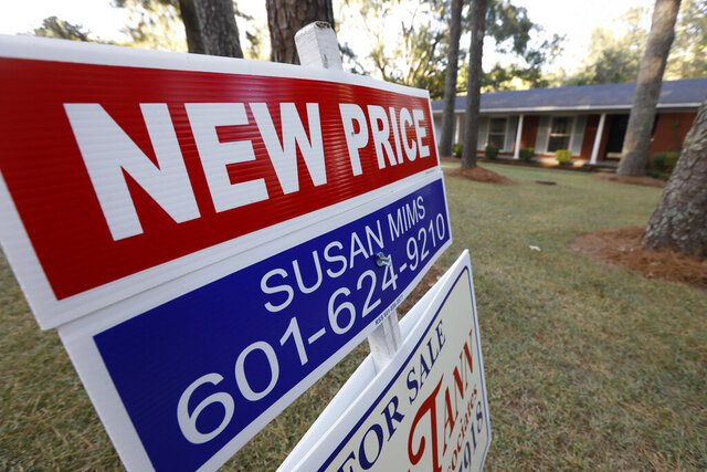 FILE - In this Sept. 25, 2019, file photo a sign indicating a new selling price for a house sits atop a realtor's sign in Jackson, Miss. On Tuesday, Nov. 26, the Standard & Poor's/Case-Shiller 20-city home price index for September is released. (AP Photo/Rogelio V. Solis, File)