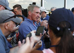 Retired NFL head coach Mike Shanahan, center, talks to reporters during a combined NFL training camp at which the Denver Broncos hosted the San Francisco 49ers Saturday, Aug. 17, 2019, at the Broncos' headquarters in Englewood, Colo. (AP Photo/David Zalubowski)