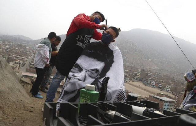 Barber Josue Yacahuanca styles the hair of a resident free of charge at the top of a hill in the San Juan de Lurigancho neighborhood of Lima, Peru, Friday, June 19, 2020.