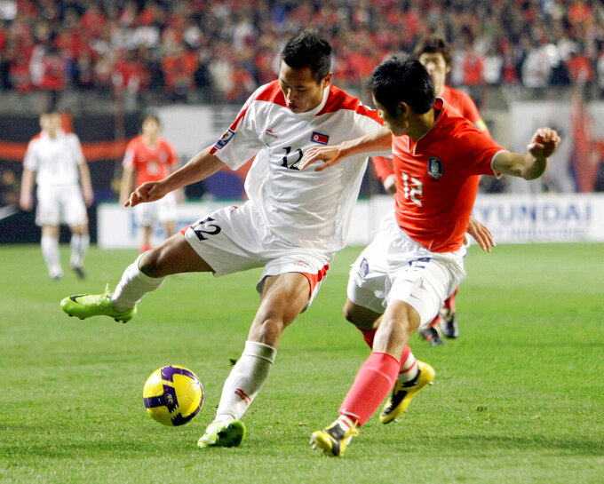 FILE - In this April 1, 2009, file photo, North Korea's Jong Tae Se, left, fights for the ball against South Korea's Lee Young-pyo during their 2010 FIFA World Cup Asia group 2 qualifying soccer match at Seoul World Cup Stadium in Seoul, South Korea. South Korean officials say North Korea has told soccer's Asian governing body it will not participate in World Cup qualifiers next month because of coronavirus concerns. Kim Min-soo, an official from the Seoul-based Korean Football Association, on Tuesday, May 4, 2021, said the Asian Football Confederation has requested North Korea to reconsider its decision. He said the North notified the AFC last week of its intent to drop out of the matches.(AP Photo/ Lee Jin-man, File)