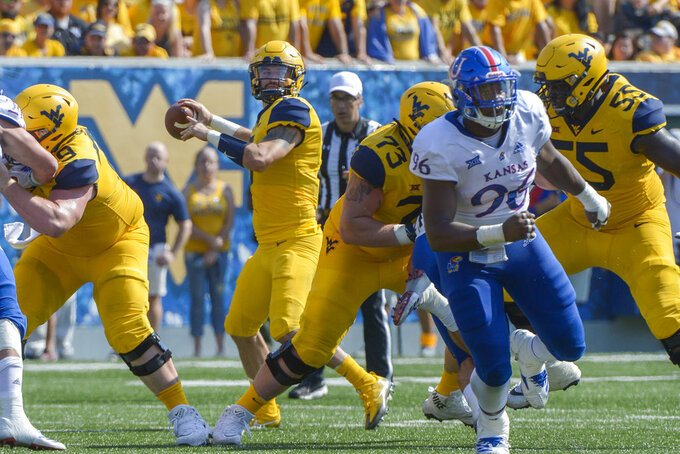 West Virginia quarterback Will Grier (7) looks for a receiver during the first half of an NCAA college football game against Kansas in Morgantown, W. Va., Saturday Oct. 6, 2018. (AP Photo/Craig Hudson)