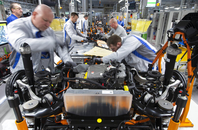 In this Tuesday, Feb. 25, 2020 file photo, workers complete an electric car ID.3 body at the assembly line during a press tour at the plant of the German manufacturer Volkswagen AG (VW) in Zwickau, Germany. The German economy shrank by 2,2 percent in the first quarter of the year compared to the same period in 2019 amid a global downturn linked to the coronavirus pandemic. Germany's Federal Statistical Office said Monday that it was the biggest quarterly decline since the 2008-2009 global financial crisis. (AP Photo/Jens Meyer)
