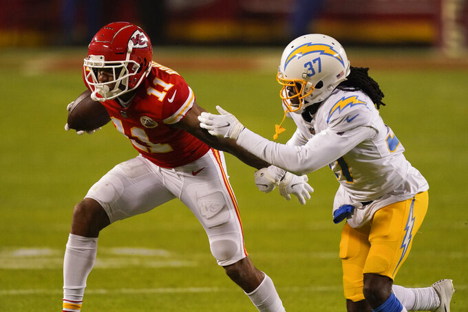 Kansas City Chiefs wide receiver Demarcus Robinson (11) runs from Los Angeles Chargers cornerback Tevaughn Campbell (37) after catching a pass during the second half of an NFL football game, Sunday, Jan. 3, 2021, in Kansas City. (AP Photo/Charlie Riedel)