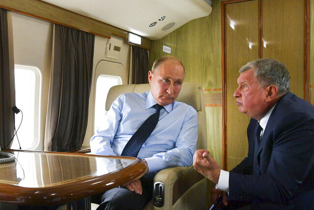 FILE - In this Aug. 27, 2018 file photo, Russian President Vladimir Putin, left, listens to Russian Rosneft CEO Igor Sechin during his flight to visit Chernigovets coal mine, in Beryozovsky, Kemerovo region, Russia. On Tuesday, Feb. 18, 2020, the Treasury Department slapped sanctions on Rosneft's trading arm and its CEO, accusing the Geneva-based firm of providing a critical lifeline to Venezuela's President Nicolas Maduro. (Alexei Druzhinin, Sputnik, Kremlin Pool Photo via AP, File)