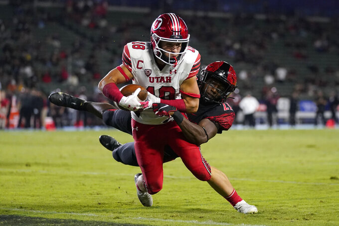 Utah wide receiver Britain Covey (18) runs to the end zone for a touchdown while being tackled by San Diego State safety Cedarious Barfield (27) during the second half of an NCAA college football game Saturday, Sept. 18, 2021, in Carson, Calif. (AP Photo/Ashley Landis)