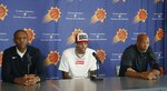 Phoenix Suns' Kelly Oubre Jr., is flanked by general manager James Jones, left, and head coach Monty Williams, right, as they all meet with the media to announce the re-signing of Oubre Jr. with the Suns NBA basketball team Tuesday, July 16, 2019, in Phoenix. (AP Photo/Ross D. Franklin)