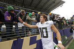 Oregon quarterback Justin Herbert greets fans after the team beat Washington in an NCAA college football game Saturday, Oct. 19, 2019, in Seattle. Oregon won 35-31. (AP Photo/Elaine Thompson)