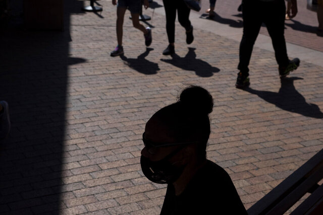 A shopper wearing a face mask sits in the shade at the Citadel Outlets in Commerce, Calif., Thursday, July 2, 2020. California Gov. Gavin Newsom on Thursday urged Californians to turn to their