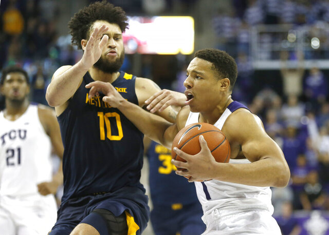 TCU guard Desmond Bane (1) is called for an offensive foul on West Virginia guard Jermaine Haley (10) during the second half of an NCAA college basketball game, Saturday, Feb. 22, 2020 in Fort Worth, Texas. TCU won in overtime. (AP Photo/Ron Jenkins)