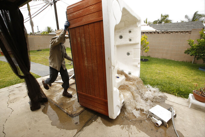 """FILE - In this May 6, 2015, file photo, professional spa remover Juan Alexander empties a spa for permanent removal at a residence in which the owner considered it """"a waste of water,"""" in Garden Grove, Calif. Gov. Gavin Newsom on Monday, May 10, 2021, declared a drought emergency for most of California, extending a previous order that affected two counties to 41 counties throughout much of the state. (AP Photo/Damian Dovarganes, File)"""