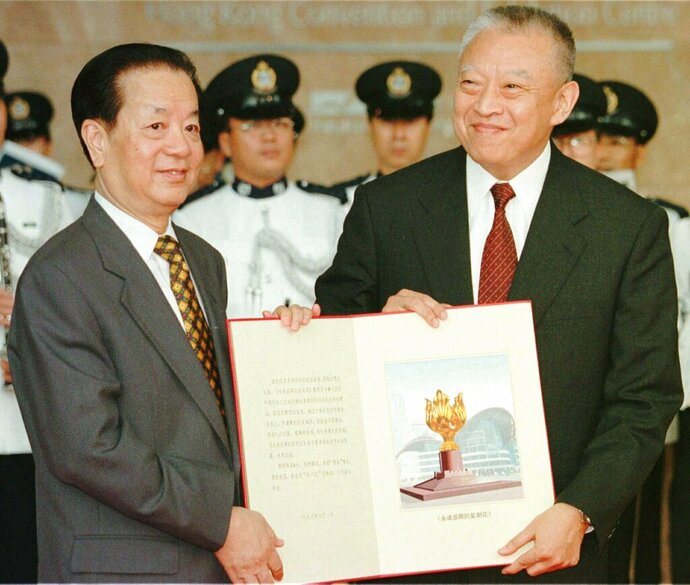 FILE - In this file photo taken Tuesday, July 1, 1997, then Hong Kong's newly inaugurated Chief Executive Tung Chee-hwa, right, receives a book bearing a picture of a statue from then Chinese Foreign Minister Qian Qichen during a ceremony in Hong Kong. On July 1, 1997, Tung Chee-Hwa, the first chief executive of Hong Kong, declared: