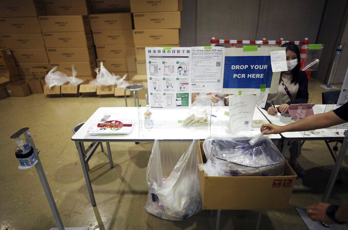 A woman drops off a test for the coronavirus infection at the Main Press Center for the 2020 Summer Olympics, Thursday, July 29, 2021, in Tokyo, Japan. About 30,000 people are spitting into tiny plastic vials every day at the Tokyo Olympics in a routine that's grown crucial in going ahead with the pandemic-era Games. (AP Photo/Hiro Komae)