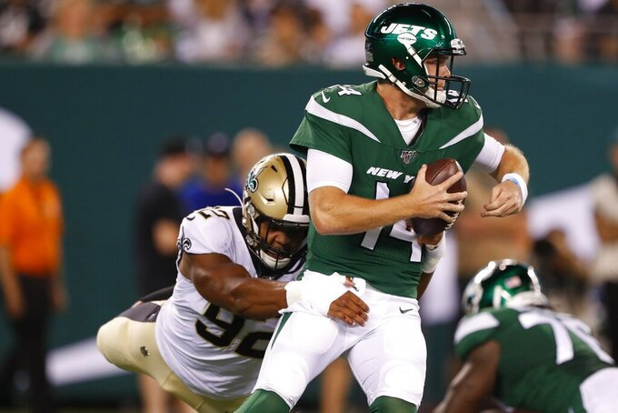 New York Jets quarterback Sam Darnold (14) breaks away from New Orleans Saints' Marcus Davenport (92) during the first half of a preseason NFL football game Saturday, Aug. 24, 2019, in East Rutherford, N.J. (AP Photo/Noah K. Murray)
