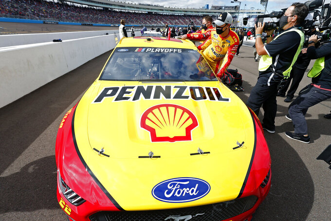 Joey Logano climbs into his race car on pit road prior to a NASCAR Cup Series auto race at Phoenix Raceway, Sunday, Nov. 8, 2020, in Avondale, Ariz. (AP Photo/Ralph Freso)