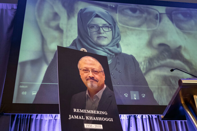 FILE - In this Nov. 2, 2018 file photo, a video image of Hatice Cengiz, fiancee of slain Saudi journalist Jamal Khashoggi, is played during an event to remember Khashoggi, who died inside the Saudi Consulate in Istanbul on Oct. 2, 2018, in Washington.  Reporters Without Borders, a press freedom group, says it has taken an unprecedented mission to Saudi Arabia to advocate for the release of 30 jailed journalists in the aftermath of the killing of Saudi writer Jamal Khashoggi. Reporters Without Borders said a small delegation led by its secretary general met with the Saudi foreign, justice and media ministers, and the public prosecutor, during a three-day visit in April to engage directly with the government on the need for urgent press freedom reforms. (AP Photo/J. Scott Applewhite, File)