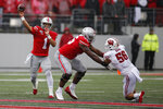 Ohio State quarterback Justin Fields, left, throws a pass as offensive lineman Thayer Munford, center, blocks Wisconsin linebacker Zack Baun during the first half of an NCAA college football game Saturday, Oct. 26, 2019, in Columbus, Ohio. (AP Photo/Jay LaPrete)