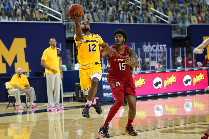Michigan Wolverines guard Mike Smith (12) drives on Rutgers center Myles Johnson (15) in the second half of an NCAA college basketball game in Ann Arbor, Mich., Thursday, Feb. 18, 2021. (AP Photo/Paul Sancya)