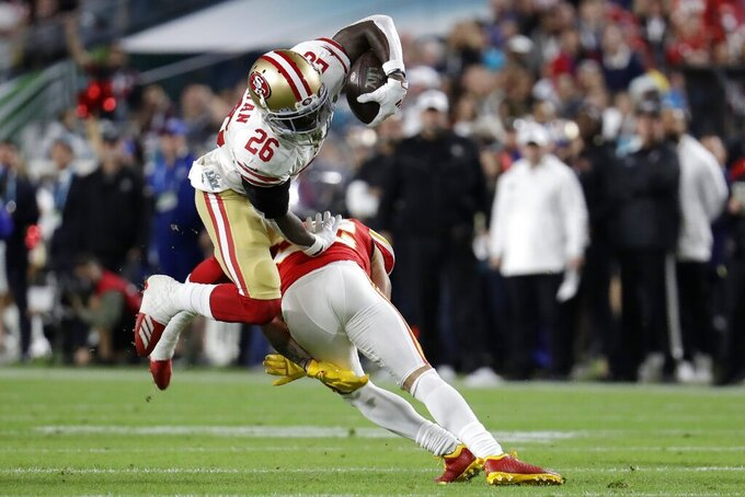 San Francisco 49ers' Tevin Coleman (26) runs against Kansas City Chiefs' Tyrann Mathieu during the first half of the NFL Super Bowl 54 football game Sunday, Feb. 2, 2020, in Miami Gardens, Fla. (AP Photo/Lynne Sladky)
