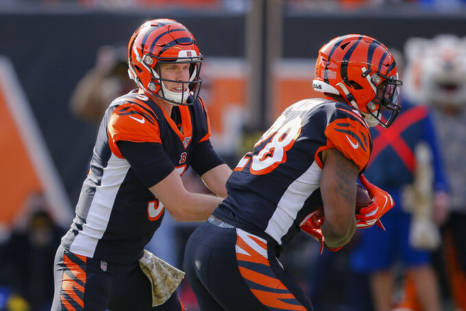 Cincinnati Bengals quarterback Ryan Finley, left, hands off the ball to running back Joe Mixon (28) during the first half of NFL football game against the Baltimore Ravens, Sunday, Nov. 10, 2019, in Cincinnati. (AP Photo/Gary Landers)