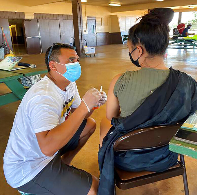 In this photo provided by Bryden Kaauwai, Dr. Kapono Chong-Hanssen administers COVID-19 vaccines, Saturday, July 10, 2020, in Kekaha, Hawaii. Chong-Hanssen supports a resolution introduced by a member of the Honolulu City Council urging Hawaii government agencies to go beyond minimum federal standards and get more specific when collecting racial data in one of the most racially diverse state in the nation. Chong-Hanssen said the pandemic underscores the need for data that doesn't lump together Pacific Islanders. (Bryden Kaauwai via AP)