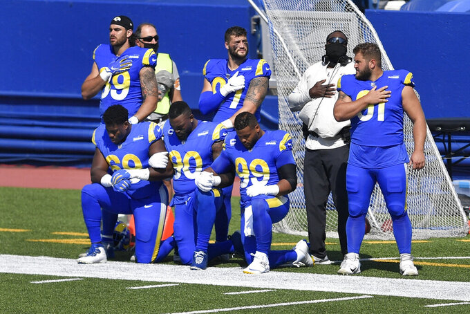 CORRECTS DATE IN NYFF101-134 TO SEPT. 27, 2020 INSTEAD OF AUG. 26, 2018 - Los Angeles Rams nose tackle Sebastian Joseph-Day (69), Michael Brockers (90) and Aaron Donald (99) take a knee during the playing of the national anthem before an NFL football game against the Buffalo Bills, Sunday, Sept. 27, 2020, in Orchard Park, N.Y. (AP Photo/Adrian Kraus)