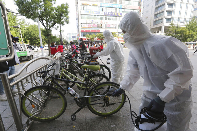 Workers and volunteers disinfect as a precaution against the coronavirus on a street in Goyang, South Korea, Tuesday, Aug. 25, 2020. South Korea is closing schools and switching back to remote learning in the greater capital area as the country counted its 12th straight day of triple-digit daily increases in coronavirus cases. (AP Photo/Ahn Young-joon)