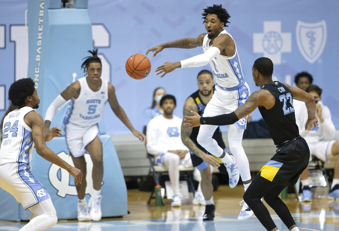North Carolina's Leaky Black (1) breaks up a pass by Marquette's Jamal Cain (23) during the first half of an NCAA college basketball game Wednesday, Feb. 24, 2021, in Chapel Hill, N.C. (Robert Willett/The News & Observer via AP)