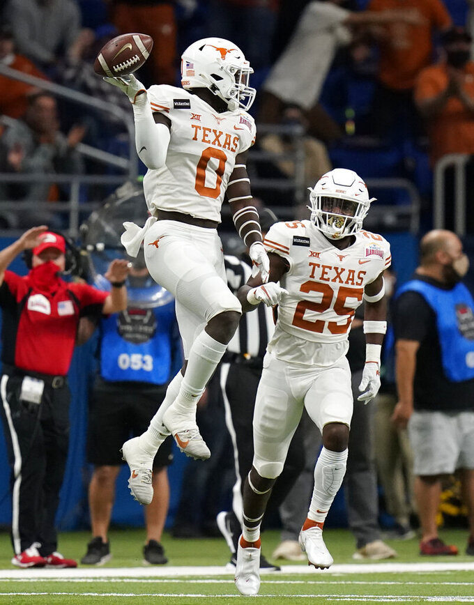Texas linebacker DeMarvion Overshown (0) celebrates after making an interception against Colorado during the first half of the Alamo Bowl NCAA college football game Tuesday, Dec. 29, 2020, in San Antonio. (AP Photo/Eric Gay)