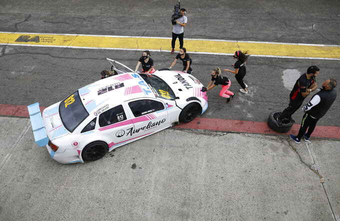 Vitarti Girl's Team mechanics, from left, Paula Salazar, Agustina Carreira, team Director Tamara Vital, and mechanic Victoria Pascual push their racing car with driver Karina Dobal at the wheel into pits after the team's first race at the Oscar y Juan Galvez track in Buenos Aires, Argentina, Sunday, April 4, 2021. The Vitarti Girl's Team is comprised of a director, engineers, mechanics and drivers, all women, and started competing in April in the Top Race Junior series. (AP Photo/Natacha Pisarenko)