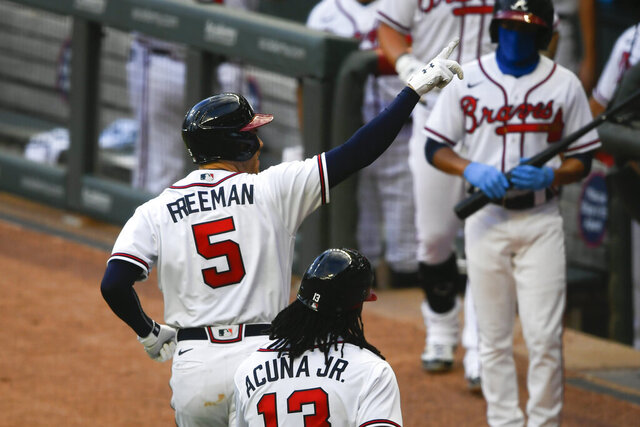 Atlanta Braves' Freddie Freeman (5) celebrates as he motions to empty seats after hitting a two-run home run during the third inning of the team's baseball game against the Tampa Bay Rays, Wednesday, July 29, 2020, in Atlanta. (AP Photo/John Amis)