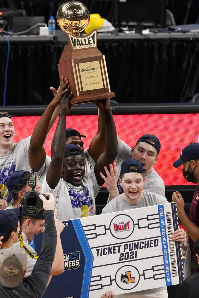Loyola of Chicago's Aher Uguak holds the trophy as he celebrates a 75-65 victory over Drake with his teammates following the championship game of the NCAA Missouri Valley Conference men's basketball tournament Sunday, March 7, 2021, in St. Louis. (AP Photo/Jeff Roberson)