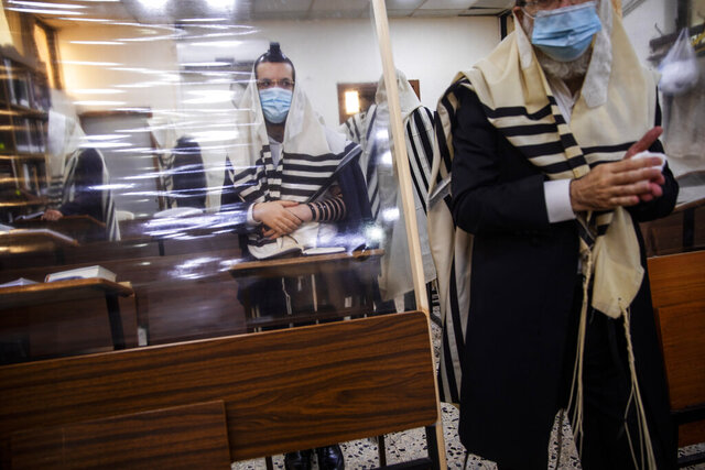 Ultra-Orthodox Jews wearing face masks during a morning prayer in a synagogue separated by plastic partitions, follow new government measures to help stop the spread of the coronavirus, in Bnei Brak, Israel, Friday, Sept 18, 2020. Israel is set to go back into a three-week lockdown later Friday to try to contain a coronavirus outbreak that has steadily worsened for months as its government has been plagued by indecision and infighting. (AP Photo/Oded Balilty)