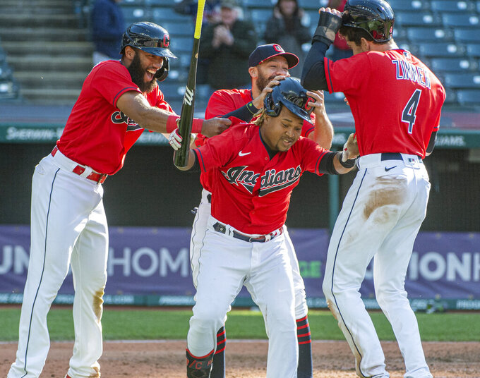 Cleveland Indians' Amed Rosario left, along with Bradley Zimmer (4) and other teammates congratulate Jose Ramirez, center, after his winning sacrifice fly off Toronto Blue Jays relief pitcher Anthony Castro during the seventh inning of the second baseball game of a doubleheader in Cleveland, Sunday, May 30, 2021. (AP Photo/Phil Long)