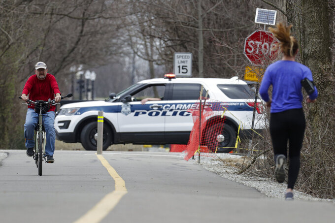 Carmel Police block a section of the Monon Trail in Carmel, Ind., Thursday, March 26, 2020. The mayor ordered a section of the trail closed to improve social distancing compliance to slow the spread of COVID-19 during Indiana's stay-at-home order. (AP Photo/Michael Conroy)