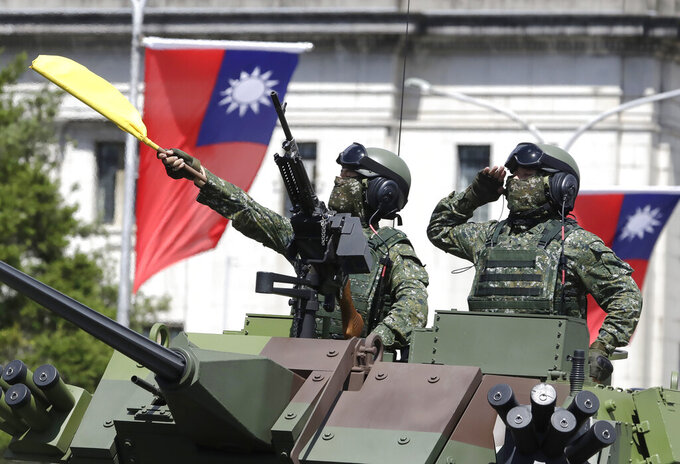 FILE - In this Oct. 10, 2021, file photo, Taiwanese soldiers salute during National Day celebrations in front of the Presidential Building in Taipei, Taiwan. After sending a record number of military aircraft to harass Taiwan over China's National Day holiday weekend, Beijing has toned down the sabre rattling but tensions remain high, with the rhetoric and reasoning behind the exercises unchanged. (AP Photo/Chiang Ying-ying, File)