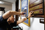 Ron Lumba, of the Alaska State Capitol's maintenance staff, adds the Majority Leader plate to the front of the office of Sen. Lyman Hoffman, D-Bethel, on the first day of the Second Special Session of the Alaska Legislature in Juneau on Monday, July 8, 2019. Divided Alaska lawmakers have found little to agree on this year, and that includes where to hold a special session. The Alaska state Senate kicked off its second special session in Juneau on Monday and promptly removed its majority leader, who was 600 miles (965 kilometers) away in Wasilla, with nearly a third of her fellow lawmakers. The first-term governor, a Republican, called for them to meet there, saying said a change of venue to the heart of his conservative base would be good for lawmakers. (Michael Penn/Juneau Empire via AP)
