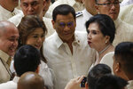 Philippine President Rodrigo Duterte, center, poses with other representatives after his 4th State of the Nation Address at the House of Representatives in Quezon city, metropolitan Manila, Philippines Monday July 22, 2019. (AP Photo/Aaron Favila)