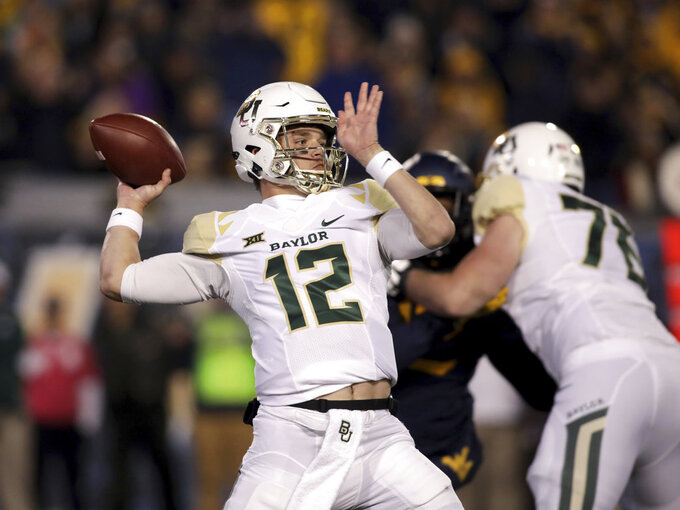 Baylor quarterback Charlie Brewer (12) looks to pass during the first half of an NCAA college football game against West Virginia, Thursday, Oct. 25, 2018, in Morgantown, W.Va. (AP Photo/Raymond Thompsonr