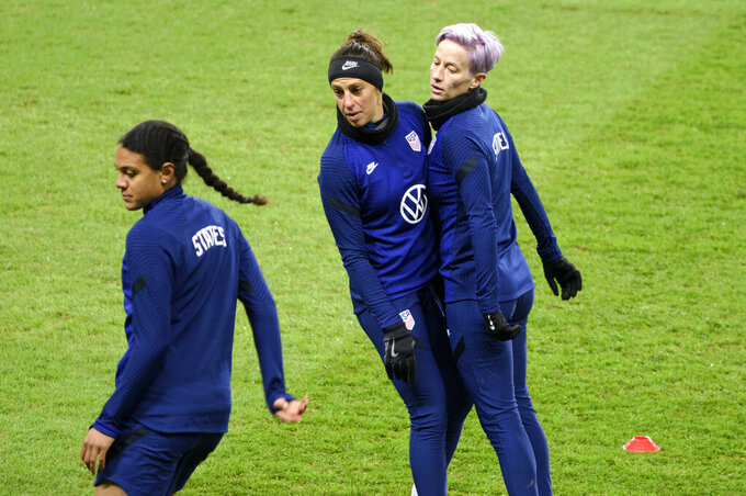 Alana Cook, left, Carli Lloyd and Megan Megan Rapinoe, right, attend a training session at Friends arena in Stockholm, Sweden, Friday April 9, 2021, ahead of the friendly international soccer match against Sweden on Saturday. (Henrik Montgomery/TT News Agency via AP)