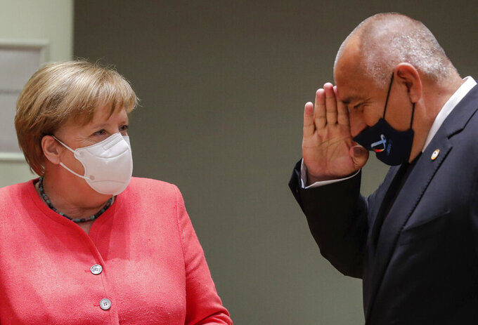 German Chancellor Angela Merkel, right, is greeted by Bulgaria's Prime Minister Boyko Borissov during a round table meeting at an EU summit in Brussels, Friday, July 17, 2020. Leaders from 27 European Union nations meet face-to-face on Friday for the first time since February, despite the dangers of the coronavirus pandemic, to assess an overall budget and recovery package spread over seven years estimated at some 1.75 trillion to 1.85 trillion euros. (Stephanie Lecocq, Pool Photo via AP)