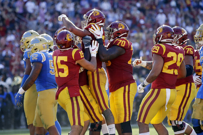 Southern California wide receiver Michael Pittman Jr., center, is lifted by teammates after his touchdown catch against UCLA during the first half of an NCAA college football game, Saturday, Nov. 23, 2019, in Los Angeles. (AP Photo/Marcio Jose Sanchez)