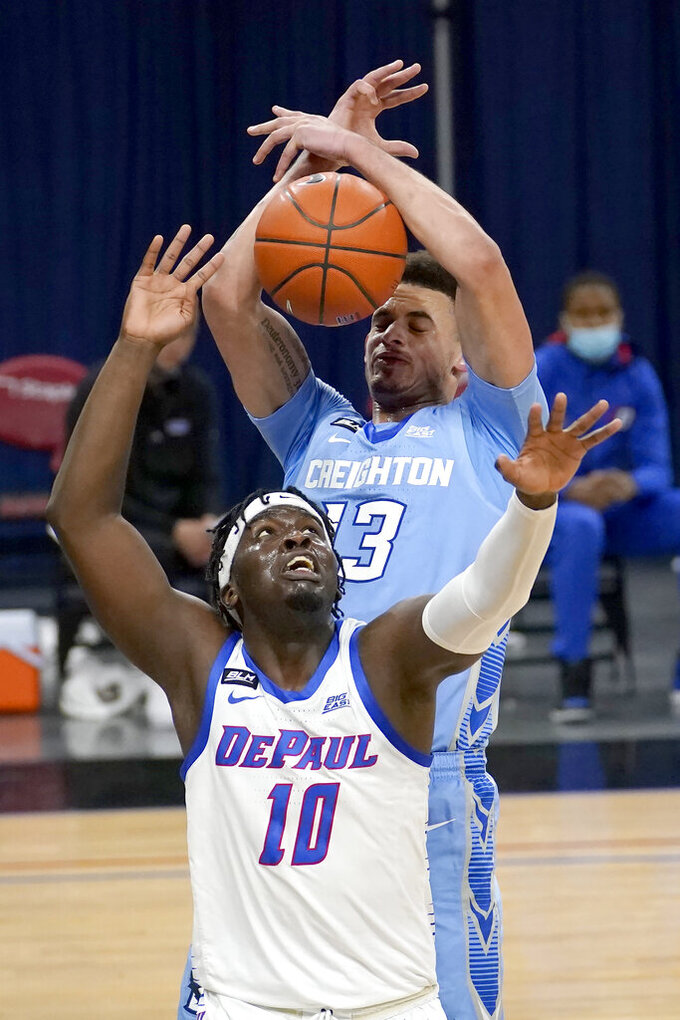 Creighton's Christian Bishop (13) grabs a rebound over DePaul's Ray Salnave during the first half of an NCAA college basketball game Saturday, Jan. 30, 2021, in Chicago. (AP Photo/Charles Rex Arbogast)