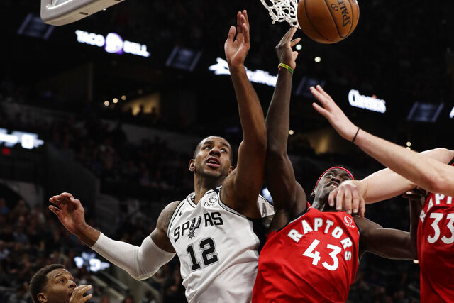 San Antonio Spurs forward LaMarcus Aldridge (12) and Toronto Raptors forward Pascal Siakam (43) scramble for a rebound during the second half of an NBA basketball game in San Antonio, Sunday, Jan. 26, 2020. (AP Photo/Eric Gay)