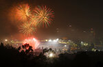 FILE - In this July 4, 2019, file photo, fireworks explode over Dodger Stadium with the Los Angeles skyline in the background following a baseball game between the Los Angeles Dodgers and the San Diego Padres in Los Angeles. With fewer professional celebrations on July 4, 2020, many Americans are bound to shoot off fireworks in backyards and at block parties. And they already are: Sales have been booming. (AP Photo/Mark J. Terrill, File)
