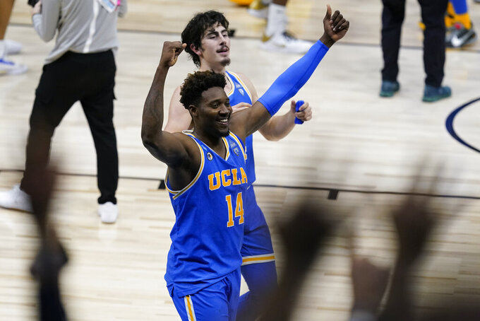 UCLA Bruins forward Kenneth Nwuba (14) and Jaime Jaquez Jr. (4) celebrate after an Elite 8 game against Michigan in the NCAA men's college basketball tournament at Lucas Oil Stadium, Wednesday, March 31, 2021, in Indianapolis. UCLA won 51-49. (AP Photo/Darron Cummings)