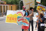 Democratic congressional candidate Teresa Leger Fernandez flashes a thumbs-up to drivers at a polling station Tuesday, June 2, 2020, in Santa Fe, N.M. Opponents in the crowded Democratic primary included former CIA operative Valerie Plame. The sign she holds,